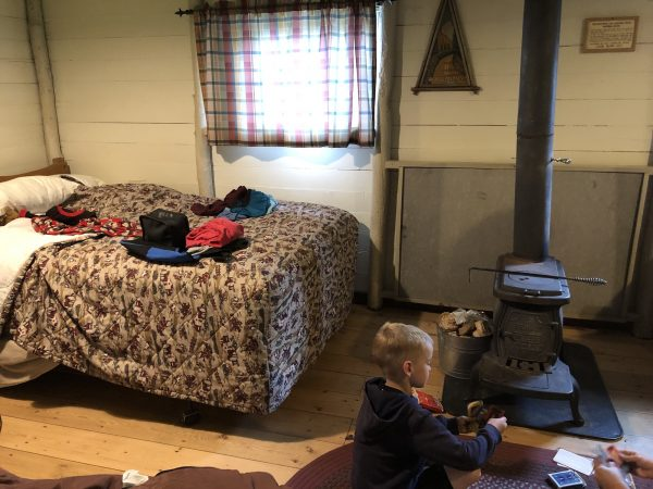 A look inside the Roosevelt cabin with bed and wood burning stove