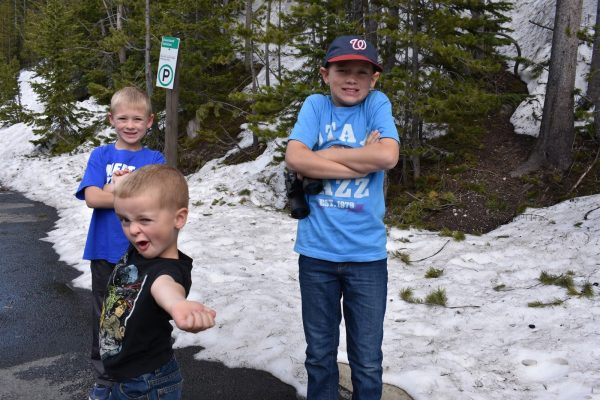 Boys standing by snow in Yellowstone National Park