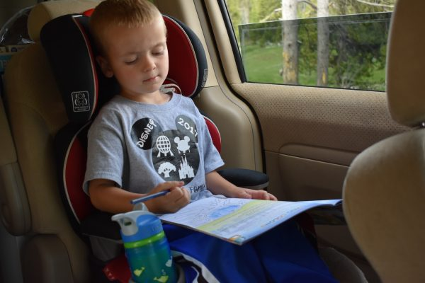 Child working on Junior Ranger booklet in car