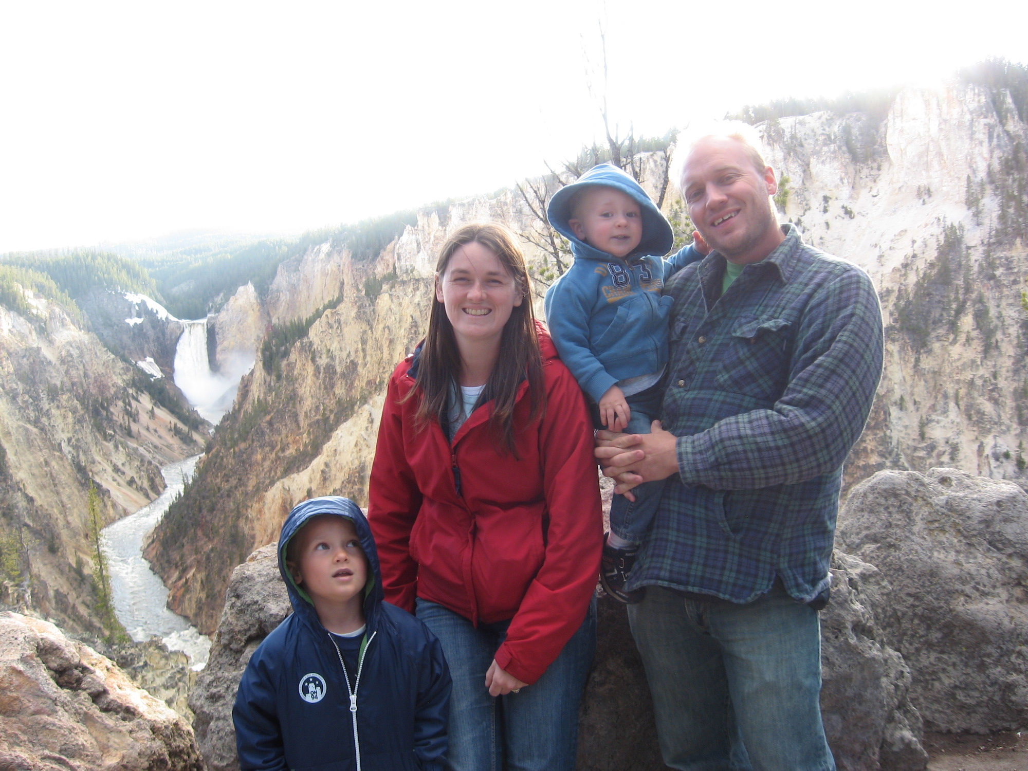 Family with Lower Falls and Yellowstone Grand Canyon in background.