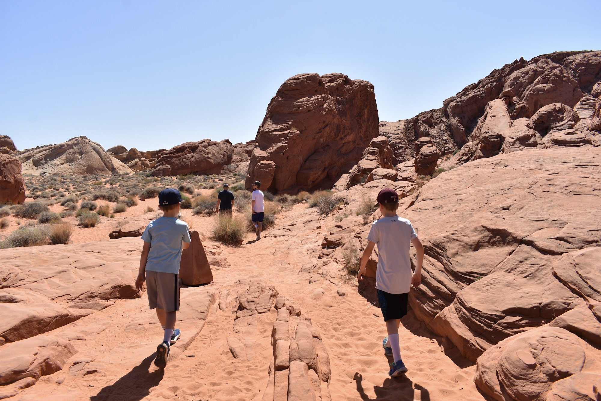 Family walking through sand on the Rainbow Vista Trail Valley of Fire state Park